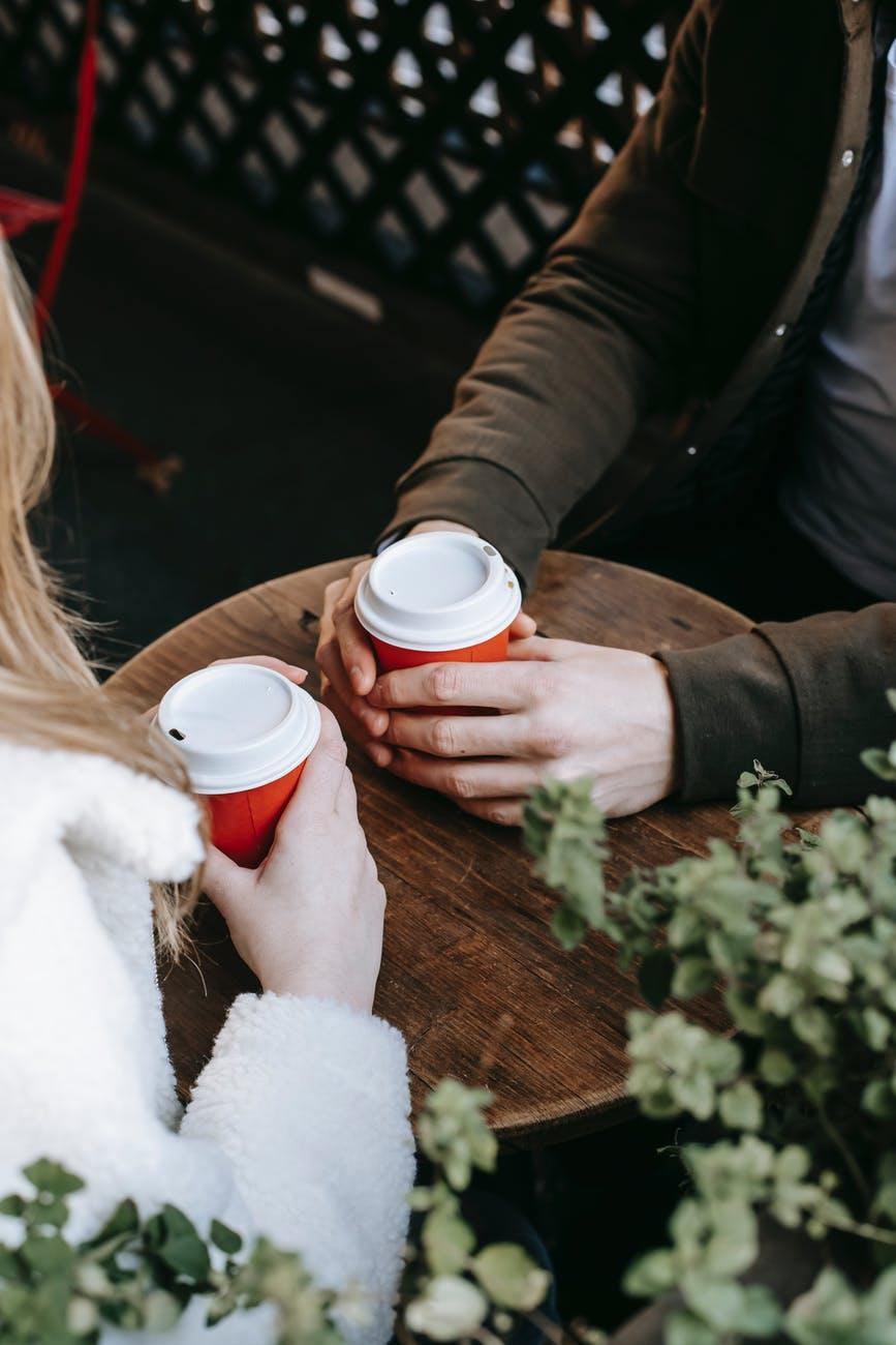 crop couple drinking coffee on terrace